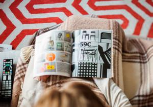 mujer ojeando un catálogo de IKEA en el salón de su casa